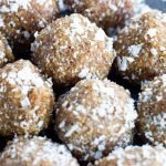 coconut date balls on a plate covered in shredded coconut