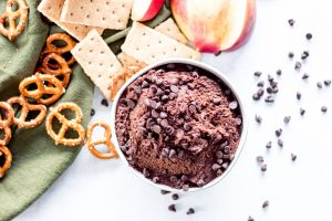 hummus dip with pretzels, crackers, and apples next to it.