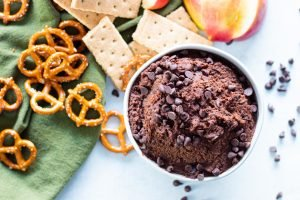 top down view of chocolate hummus with pretezels, crackers, and apples