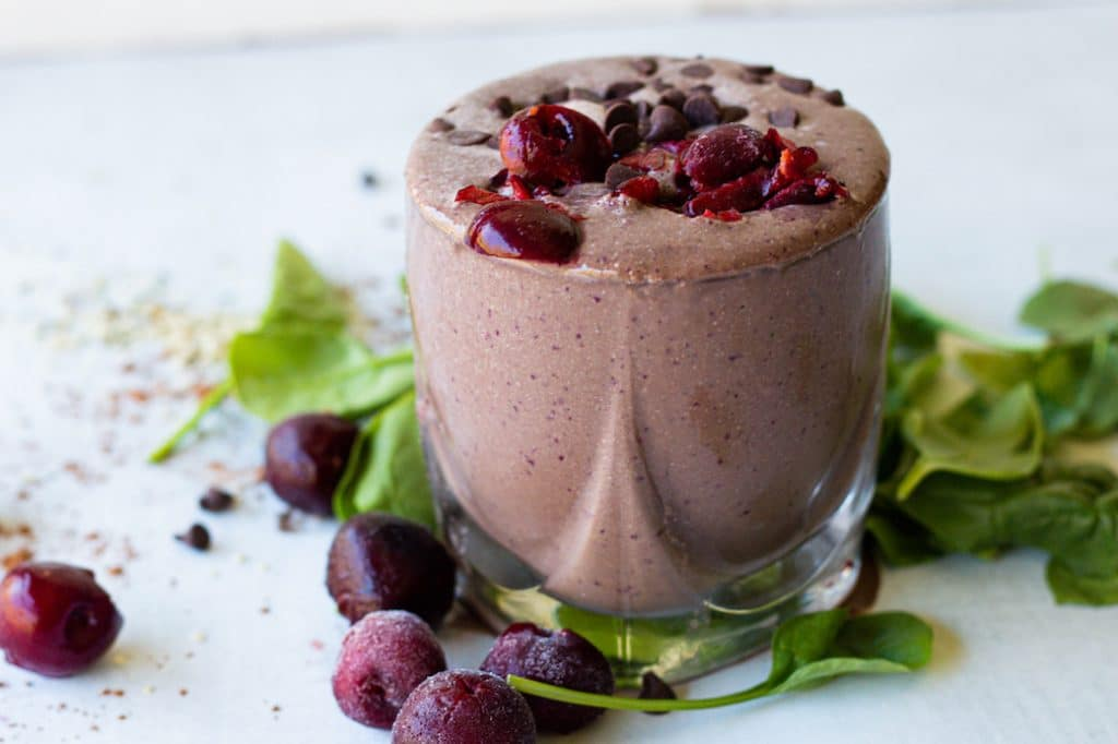 cup of chocolate cherry smoothie. Spinach and frozen cherries at foot of cup. Garnished with chopped cherries and chocolate chips