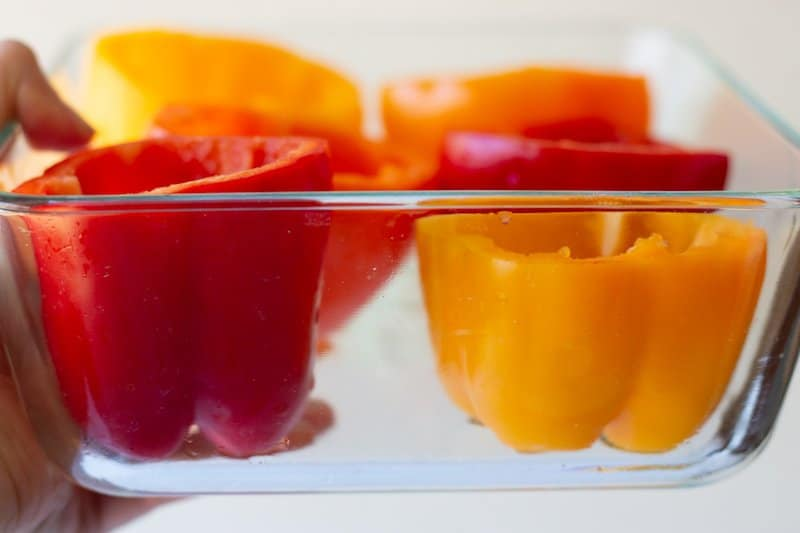 red, yellow, and orange peppers with the tops cut off in a shallow dish of water.